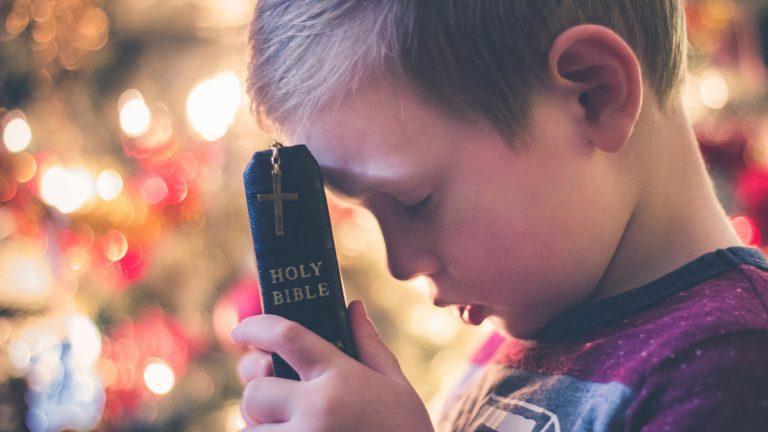 young boy with blond hair holds top of Bible to his forehead while praying in front of a Christmas tree