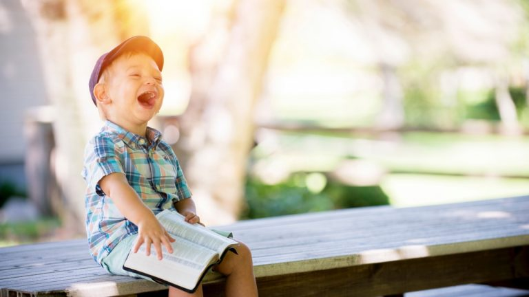 child sits with happy smile and a Bible open on lap