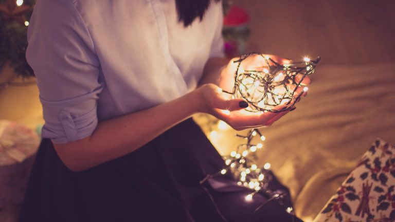 young lady with simple blouse and long skirt sits on floor with lit christmas lights cupped in her hands