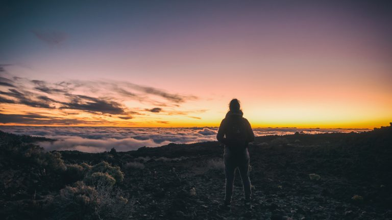 end of hike, top of mountain, woman gazes at golden yellow, orange and pink sunrise with a few thin cloud wisps on the left