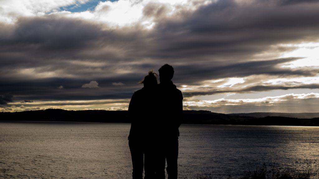 we will get through this together woman and man stand together near a large lake at dark dawn clouds and a little golden sun shows - marriage counseling